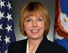 Image of Terri Sanchez; Sanchez has light blond hair and is seated before an American and U.S. Air Force Flag. She has an open mouth smile, showing her teeth.