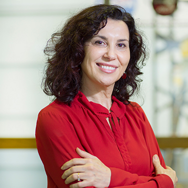 Image of Dr. Begoña Vila; Vila is standing with her arms crossed. She is smiling with her teeth showing, wears a red shirt, and has wavy dark hair that reaches her shoulders.