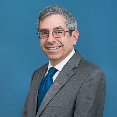 """Dr. Mark Lewis stands in front of a blue background. He has a gray suit with a blue tie and an """"NDIA"""" badge. He has gray-brown hair, glasses, and is smiling with his teeth showing."""