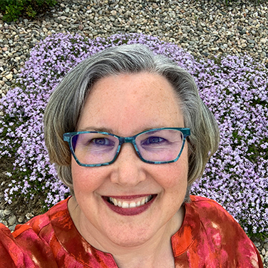 Jacqueline Maldonado is outside with purple and yellow flowers behind her. She has gray hair, a bright red shirt on, blue glasses, and is smiling with her mouth open.