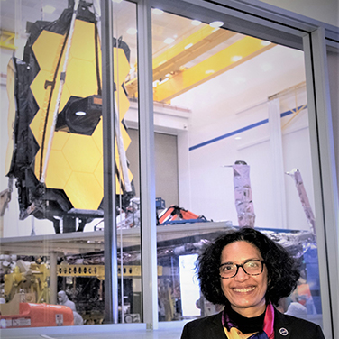 Bhavya Lal is standing before the James Webb Telescope. She has a dark shirt, dark glasses, and dark hair, and is smiling with her teeth showing.