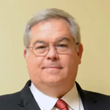 Image of Jim Moore. More is standing in front of a beige wall, has graying hair, round glasses, and has a closed mouth smile. He wears a dark suit with a red tie.