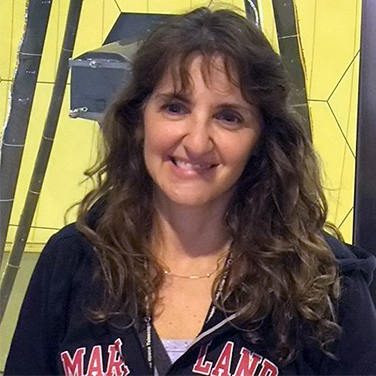 "Sandra Irish is wearing a ""Maryland"" sweatshirt jacket, has curly brown hair, and is smiling showing her teeth."